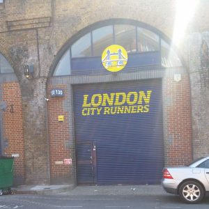 """London City Runners 2019 clubhouse closed. Blue garage type metal door with yellow """"London city runners"""" written across and yellow London bridge logo."""